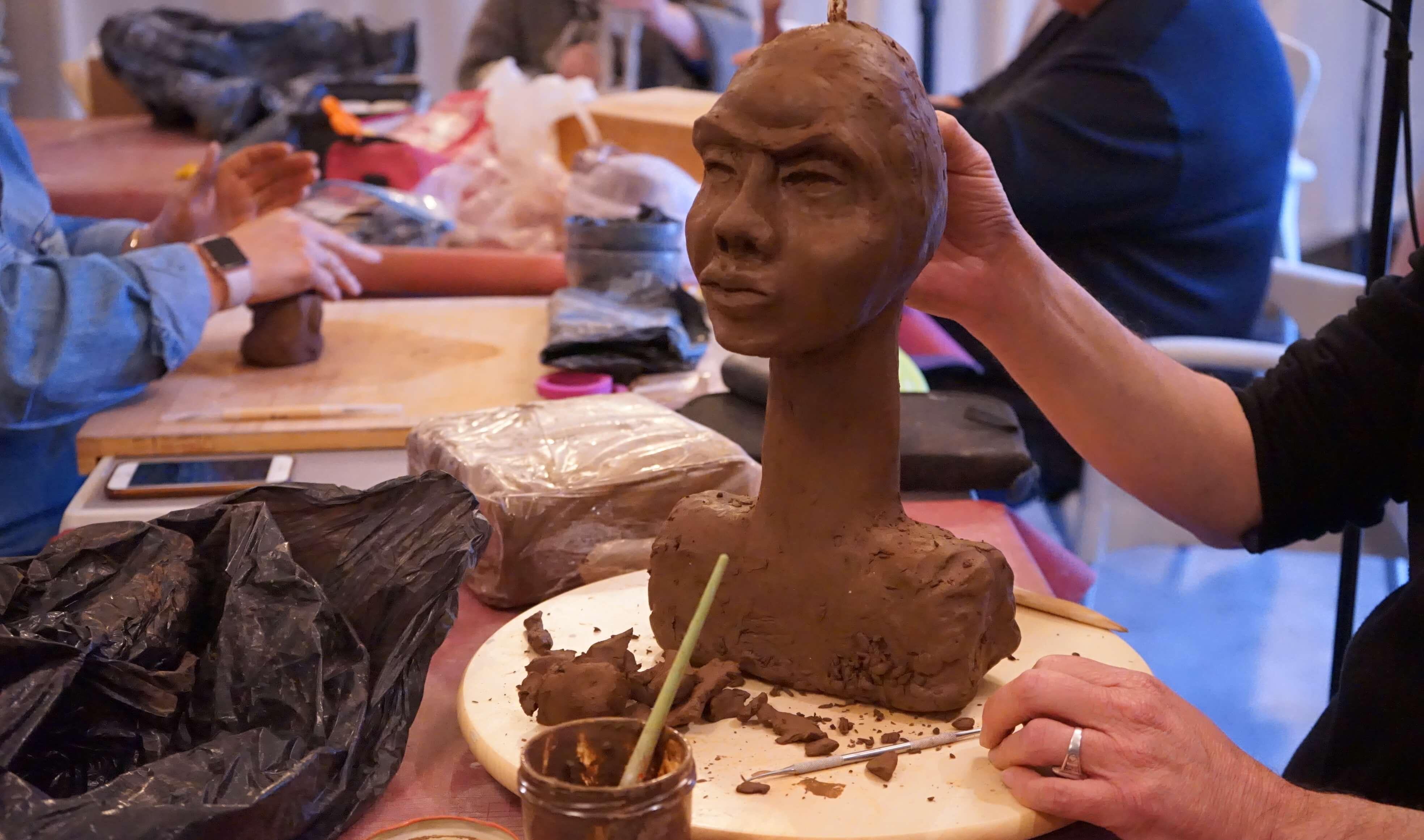 Un homme réalise une sculpture mors de l'atelier modelage en terre.